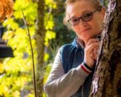 Photo of elderly woman behind a tree in nature