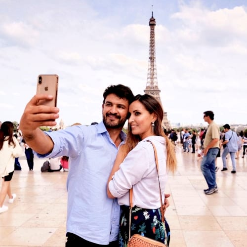 Photo of couple doing selfie in front of Eiffel Tower in Paris