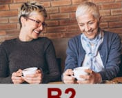 Photo of two women smiling and having a conversation at a café