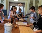 Photo of French students and teacher gathered around in kitchen learning how to use torch
