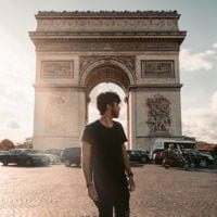 Photo of young man standing in front of Arc de Triomphe in Paris