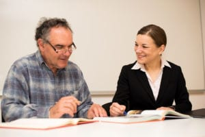 Photo of older man being tutored by younger woman