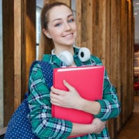 Photo of high school student with headphones, red binder and backpack