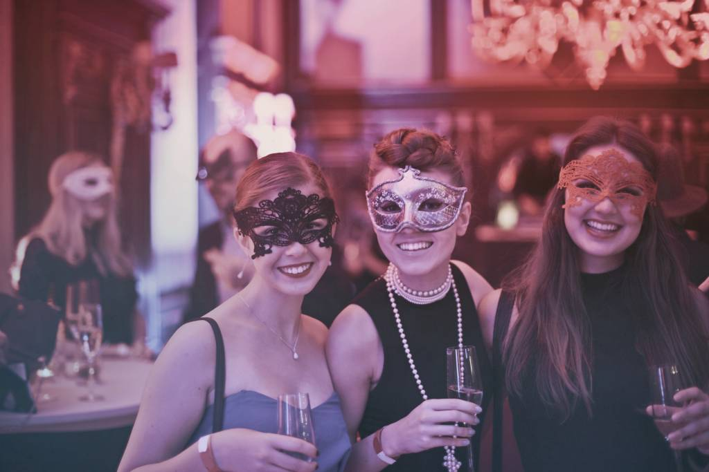 Image of three women wearing masks for Mardi Gras at a restaurant