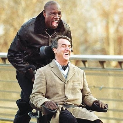 """Image of Omar Sy pushing François Cluzet in wheelchair. Scene in French movie """"Untouchables"""""""